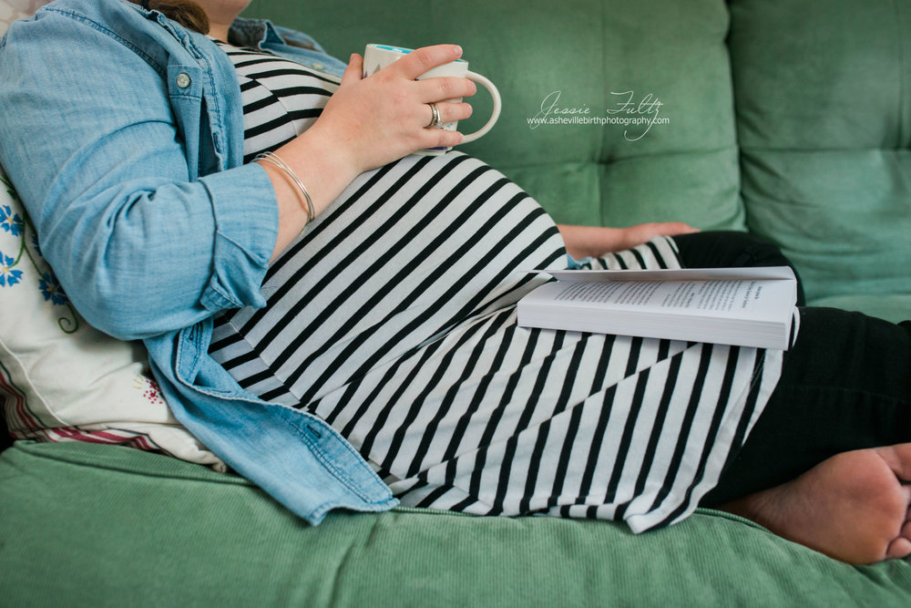 close-up picture of a pregnant woman in a striped dressresting her coffee mug on her belly and a book in her lap