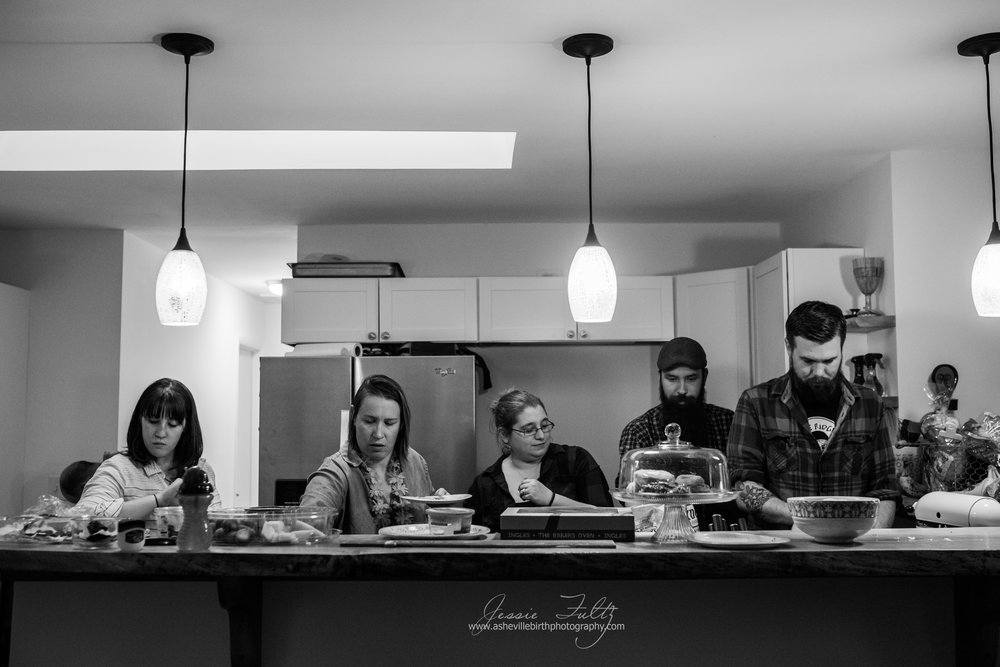 a wide-angle black and white picture fo a group of friends standing behind a kitchen bar