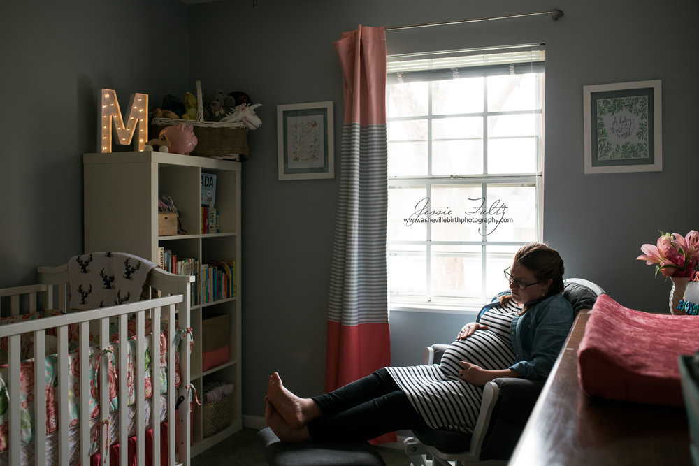 wide-angle picture of pregnant woman sitting next to a window in a glider inside her nursery