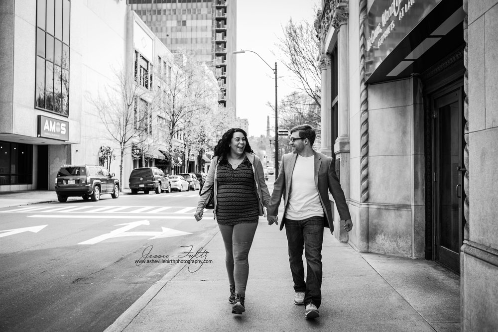black and white picture of pregnant woman and husband walking in downtown Asheville, NC
