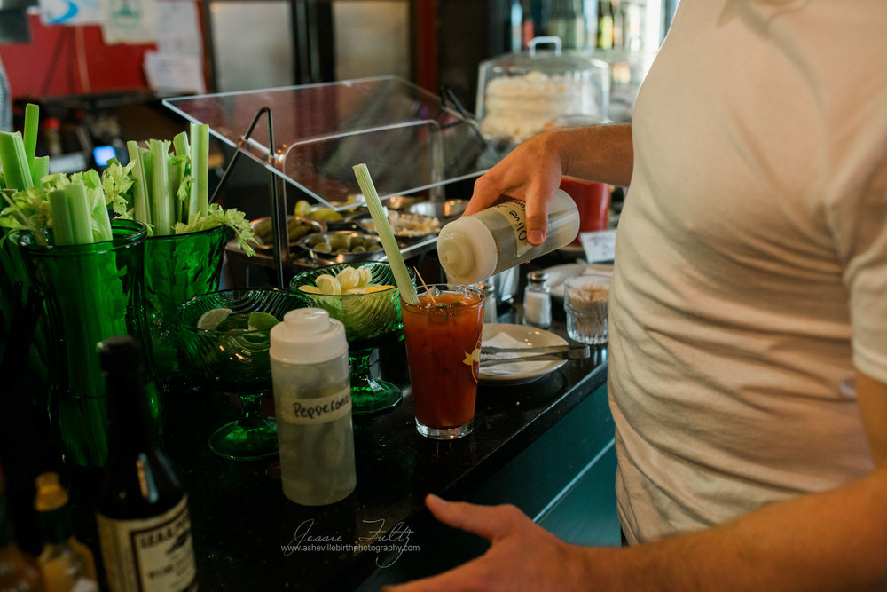 close up of a man mixing a bloody mary drink