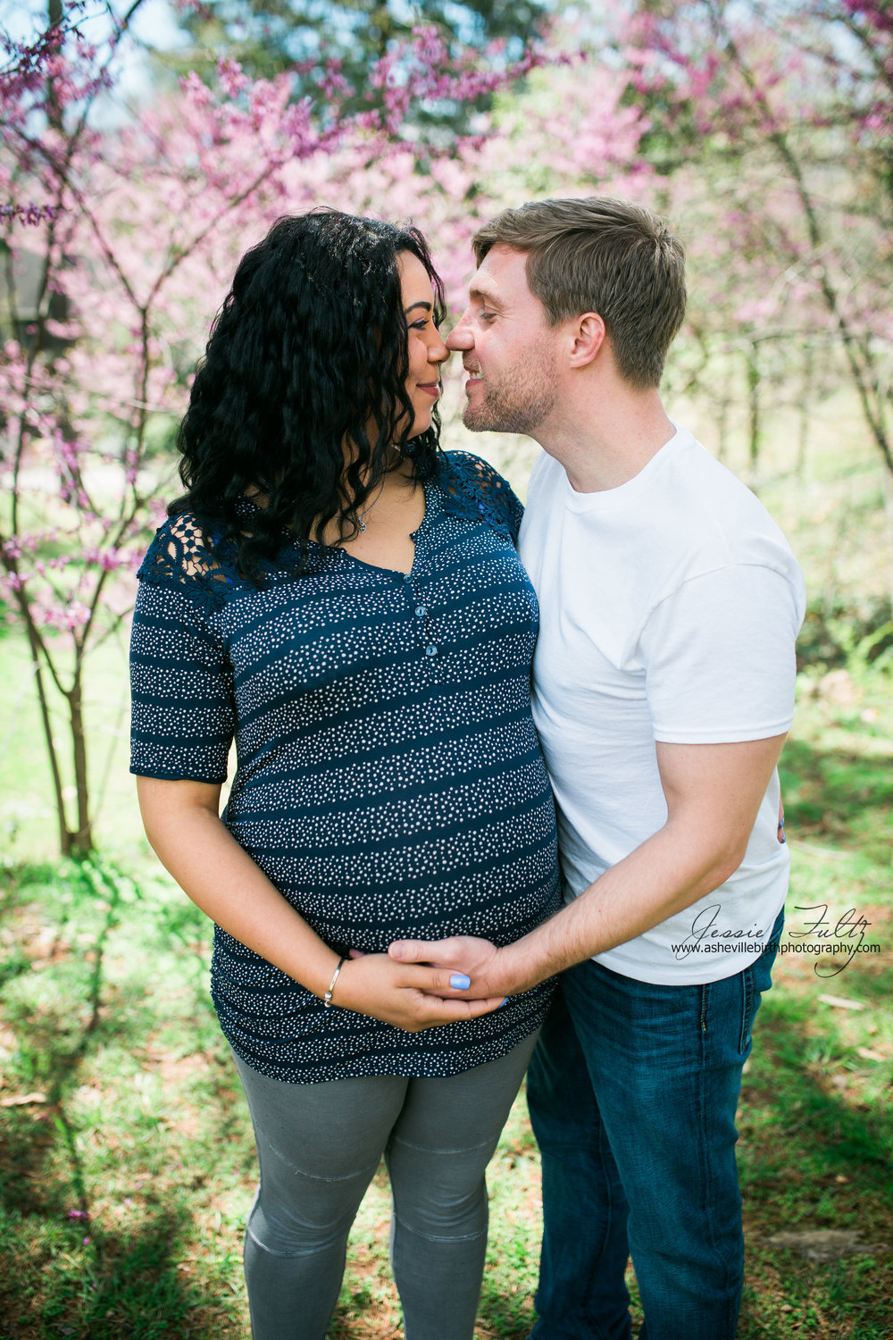pregnant woman and her husband rubbing noses in front of cherry blossoms