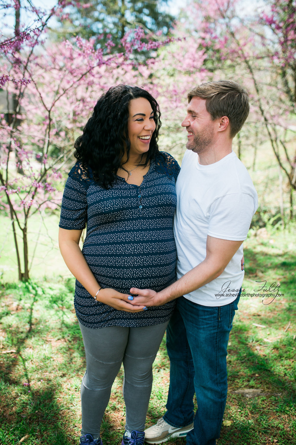 pregnant woman and her husband standing in front of cherry blossoms