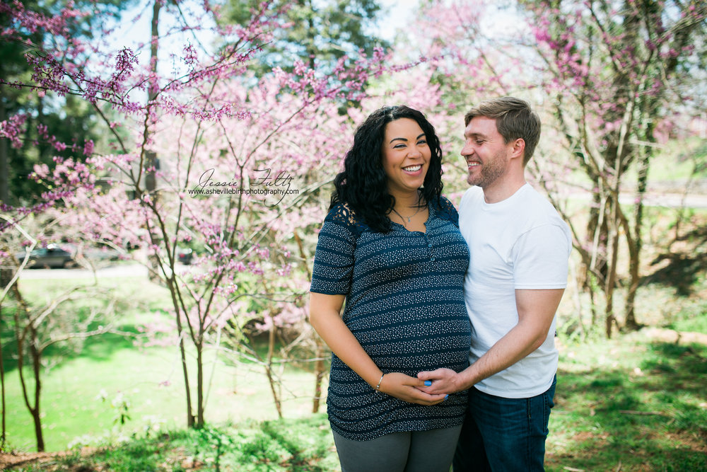 pregnant woman and her husband laughing while standing in front of cherry blossoms