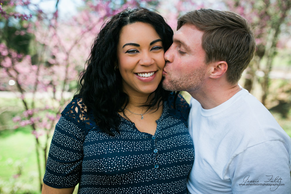 husband kissing his pregnant african-american wife on the cheek while she smiles at the camera