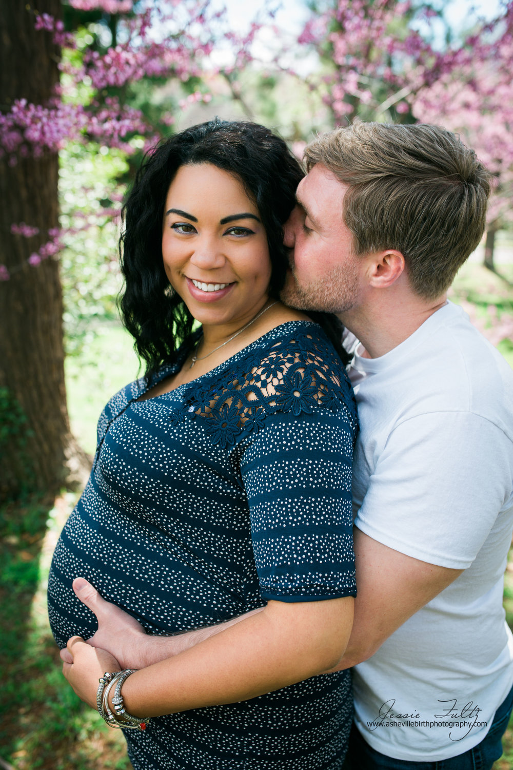 husband standing behind pregnant African-American wife with his hands on her belly kissing her cheek