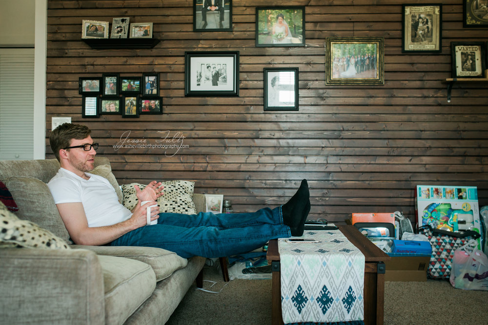 man in white t-shirt and jeans sitting on a couch next to a wood paneled wall drinking coffee