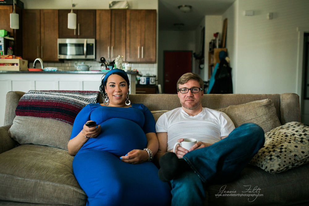 Pregnant African-american woman in a blue dress and her husband sitting on the couch watching TV
