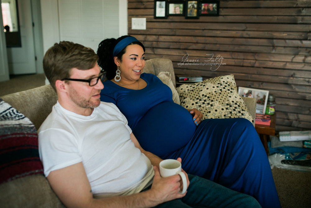 pregant african-amerian woman in a blue dress and her husband sitting on the couch watching TV