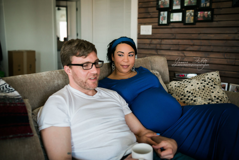 pregnant woman in a blue dress looks over at husband while sitting on the couch