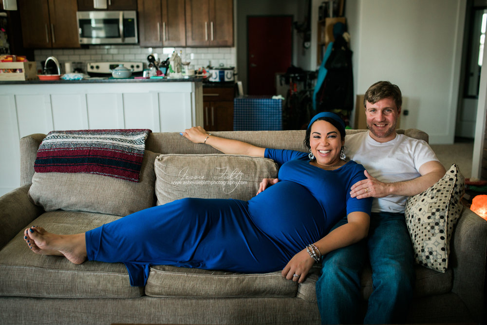 pregnant woman in blue dress laying on couch against her husband and smiling at the camera