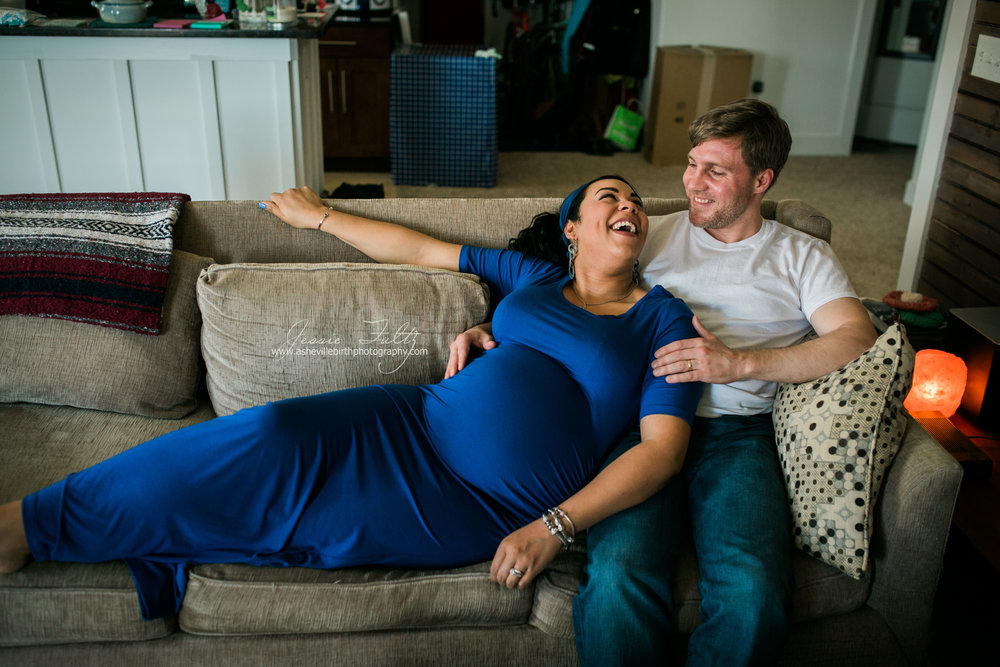 pregnant woman in blue dress laying against husband on couch looking up at him and laughing