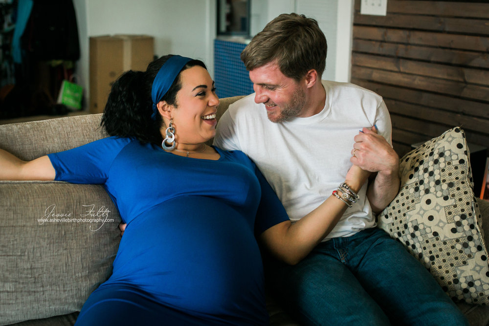 pregnant woman in a blue dress and husband sitting on a couch smiling at each other