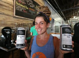ATHENS: Tour staff employee Sara Fleetwood serves up two 32 ounce crowlers to go at the Creature Comforts Brewing Company