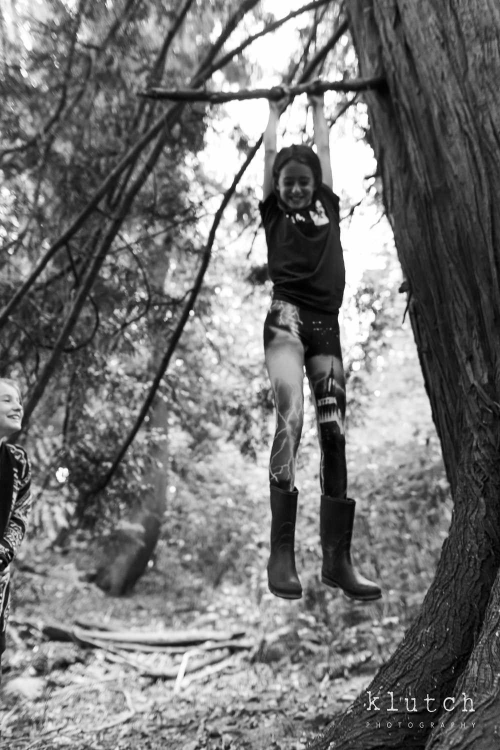 Girl dangling from tree branch