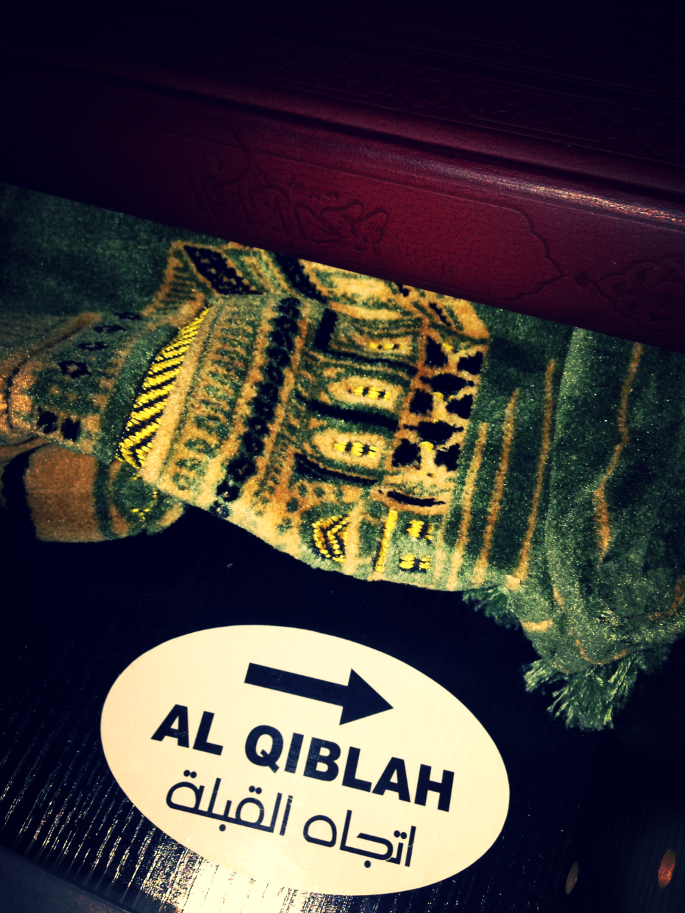 Quran, prayer rug, and direction of Mecca in a drawer in the hotel room.