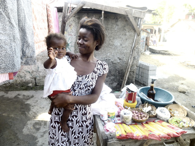 A mom with her once severely malnourished child, standing in front of the business she now runs outside of her Cap Haitian home.