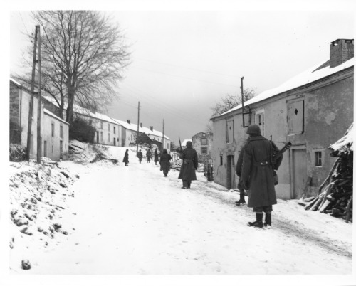 On the lookout for German snipers, a squad of Third Army Infantrymen move cautiously through the streets of Moircy, Belgium. 12/31/44. Co. C, 1st Bn., 345 Reg't., 87th Inf. Div.