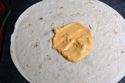 start by spreading the salsa con queso in the center of the flour tortilla.