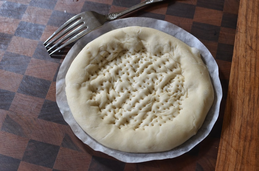 "the dough is flattened and ""docked"" with a fork"
