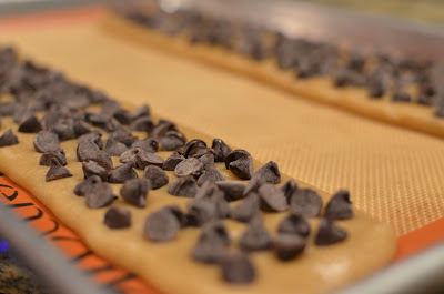 Chocolate chips are gently pressed into the cookie dough before baking.