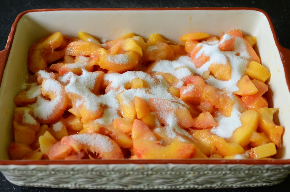 Add the sliced peaches and sprinkle with sugar.