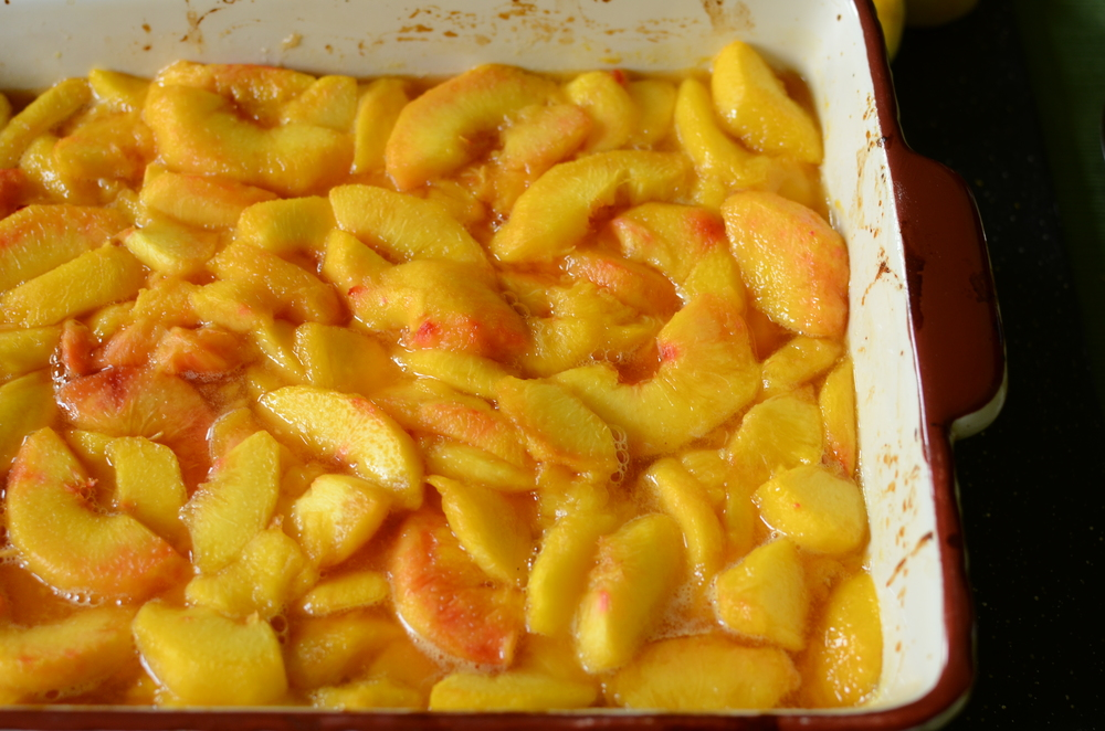 By now the peaches have baked for 20 minutes so take them out of the oven.  See all those yummy juices they started to release.  Yum!