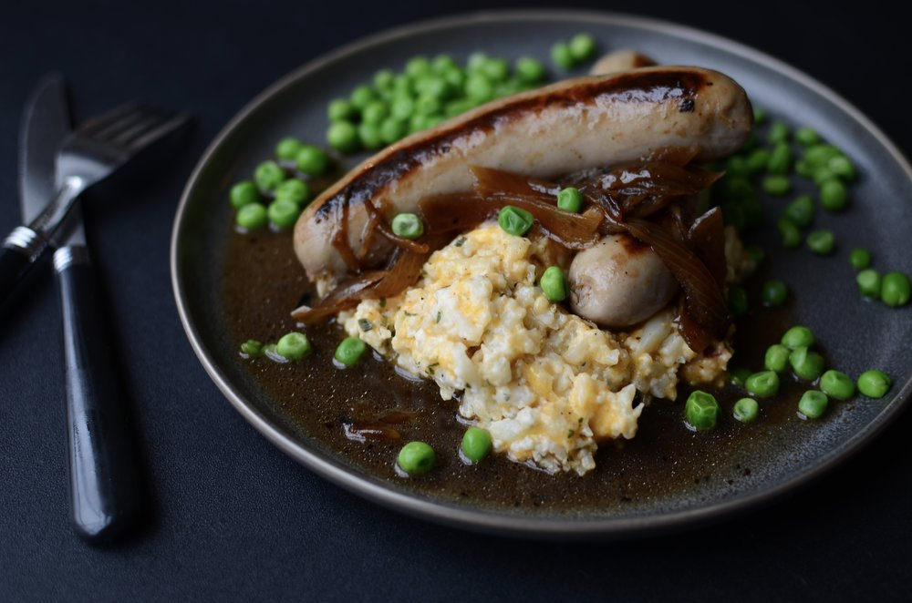 ketogenic bangers and mash recipe. how to make bangers and mash Keto-friendly. recipe for keto bangers and mashed cauliflower. keto recipes for st. Patrick's day. keto st. Patrick's day recipes. how to eat keto on st. Patricks day. Irish-style bangers and mash recipe. keto bangers and mash with onion gravy recipe. loaded mashed cauliflower recipe. keto mashed cauliflower recipe.