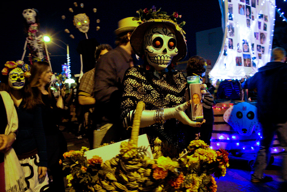 A masked woman holds a lit candle featuring the image of a loved one at the All Souls Procession parade on 4th Avenue in Tucson, Ariz., on Nov. 7, 2010. Thousands marched through downtown for the All Souls Procession, an annual event that honors Day of the Dead.