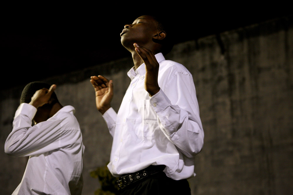Rendy Vincent, a Haiti earthquake survivor, raises his palms as he prays during the vigil and prayer service held on the eve of the one-year anniversary of the tragedy at the Manno Sanon Stadium in Miami on Tuesday, Jan. 11, 2011.