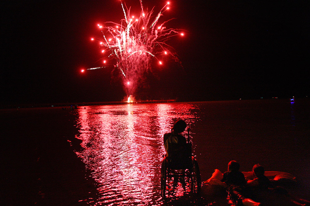 Ian Ybarra, 10, Aoghdan Potter, 12, and Savana Meiners, 6, watch the fireworks show at a beach in Port O'Connor on Saturday, July 2, 2011.