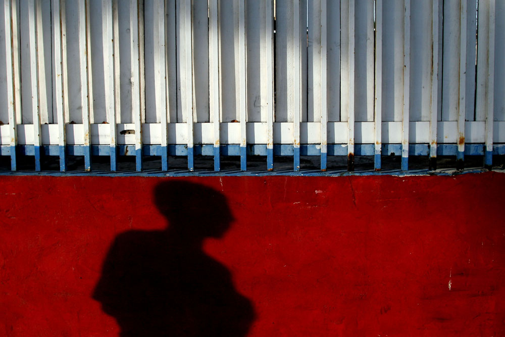 "A man's shadow falls against a wall on Southwest 8th Street, also known as ""Calle Ocho,"" in Little Havana in Miami on Monday, Jan. 10, 2011. While the area has dozens of local businesses owned by Cubans, many properties are vacant and remain for sale or lease."
