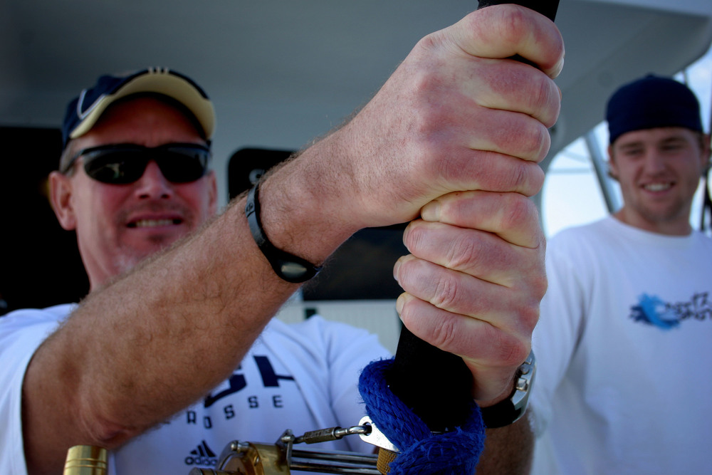 Bob Cully, 51, tightly grips a fishing rod while Tyler Andersen looks on as Cully struggles to reel in a fish. After more than half an hour of fighting, the fish managed to snap the line and escape.