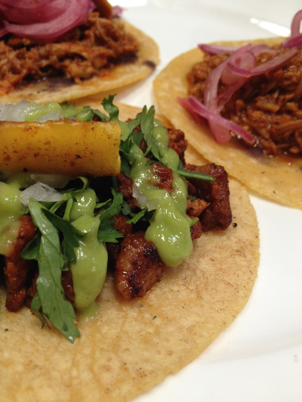 (foreground) Al Pastor taco with adobo-chile rubbed pork shoulder, pineapple, and avocado (background) Two Cochinita Pibil tacos with pulled pork shoulder, pickled red onion, oregano, habanero, and black beans