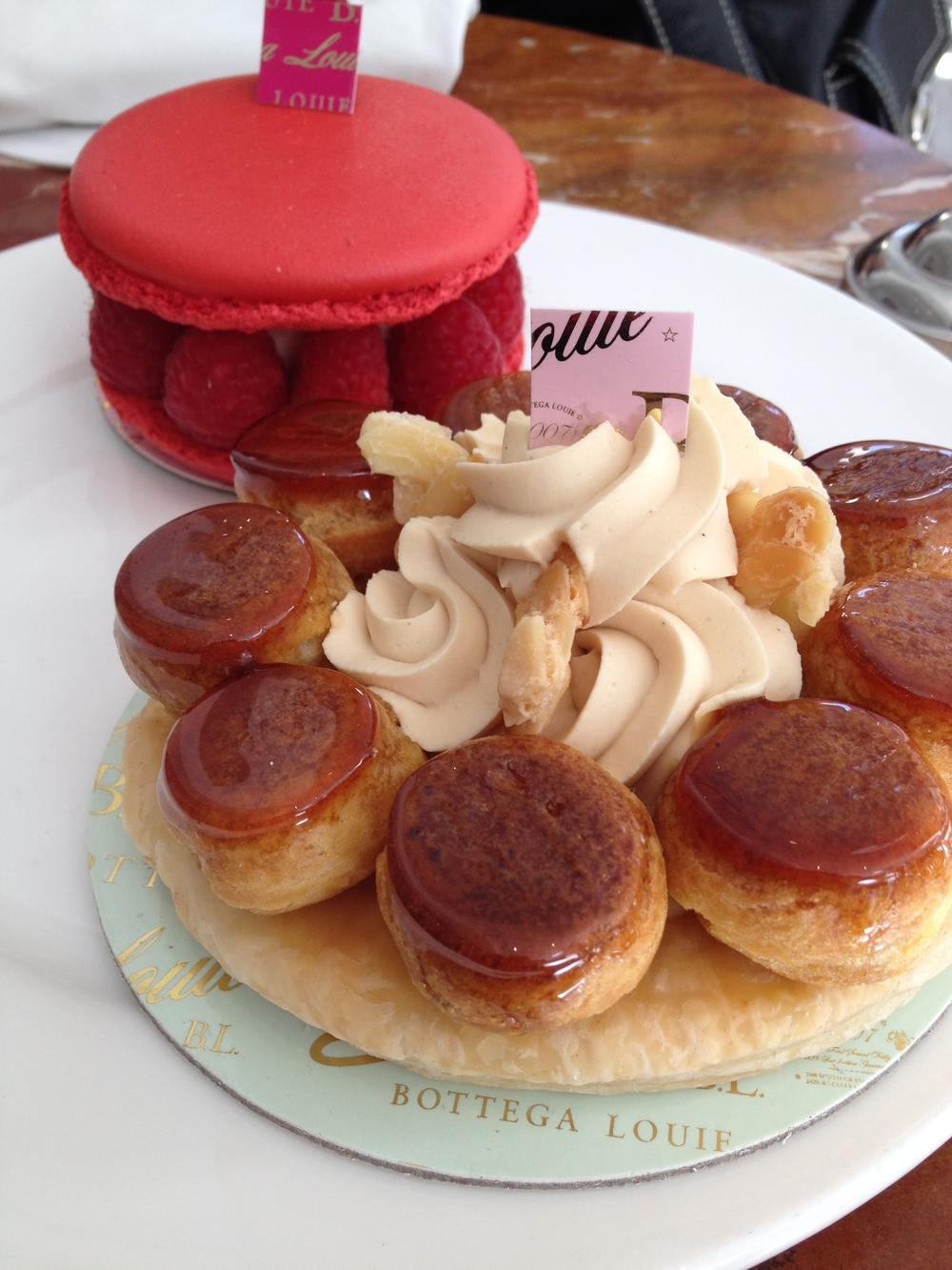 (Background) Le Grand Macaron, a French almond cookie with vanilla cream, raspberry jam, and raspberries  (Foreground) St. Honoré cake  with a base of puff pastry, cream puffs, and a ring of piped pâte à choux.