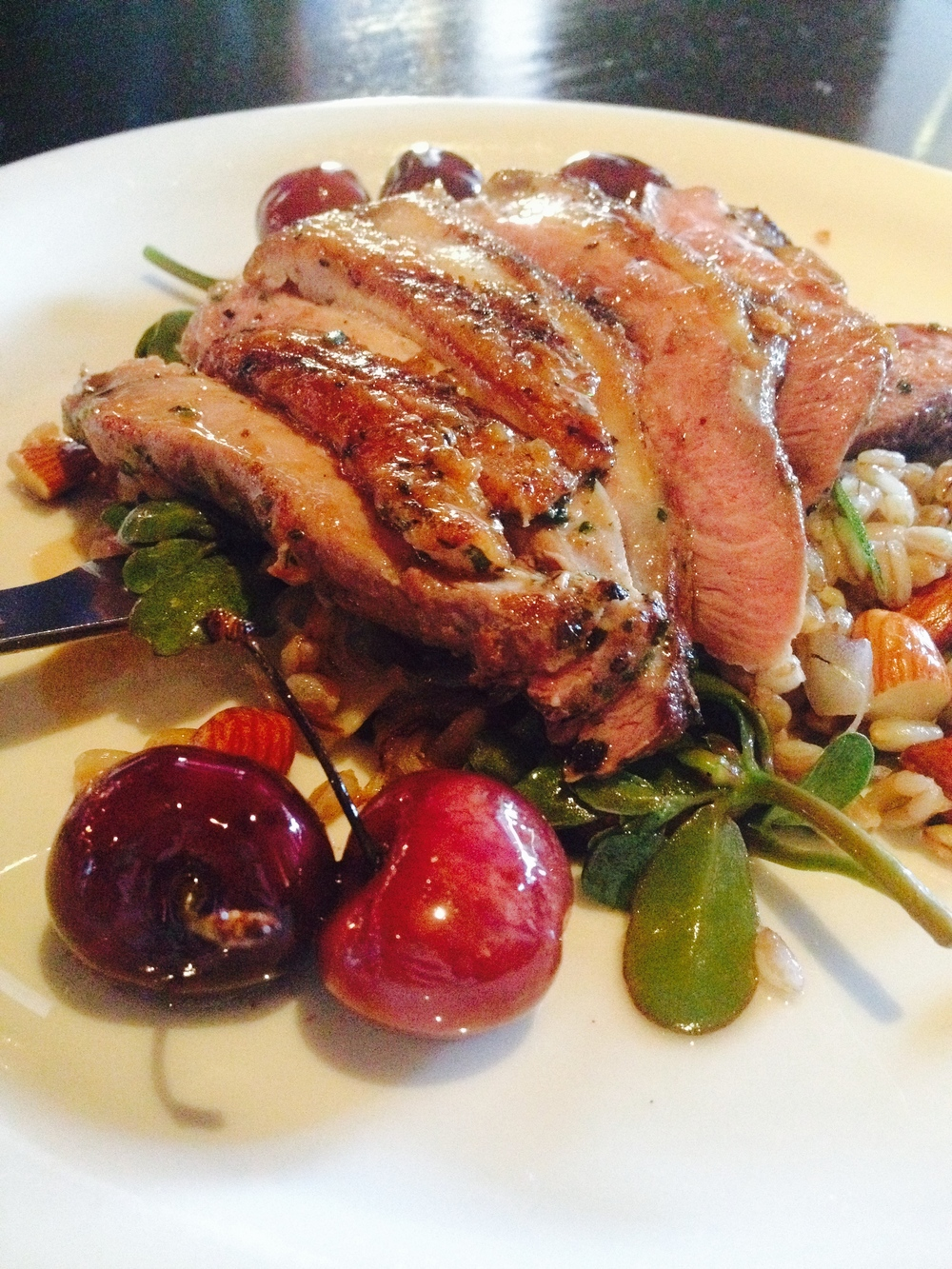 California duck breast with sautéed farro, purslane, roasted cherries, and toasted almonds.