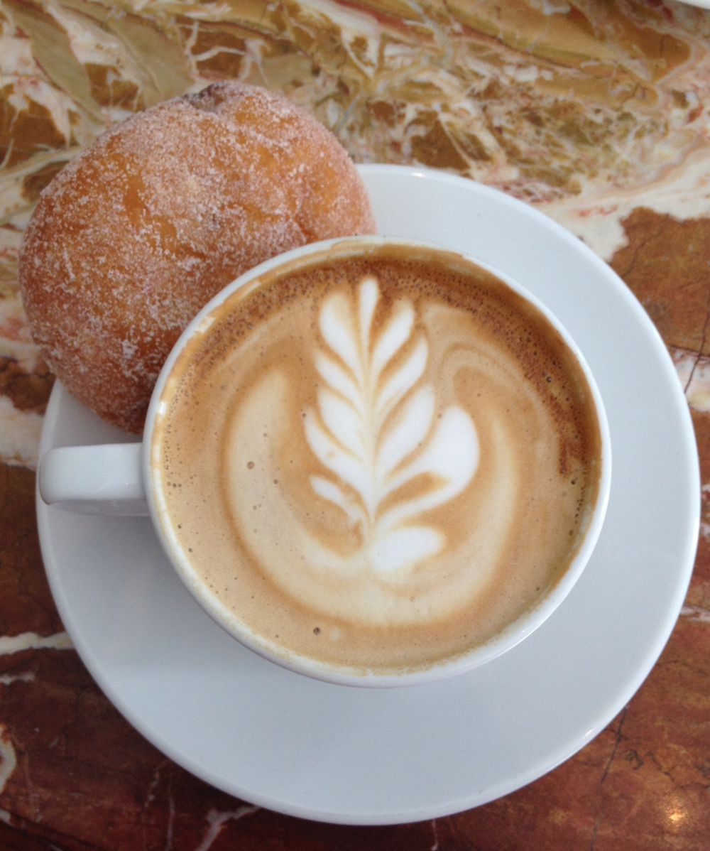 A cappuccino paired with a fresh Nutella-filled  beignet.