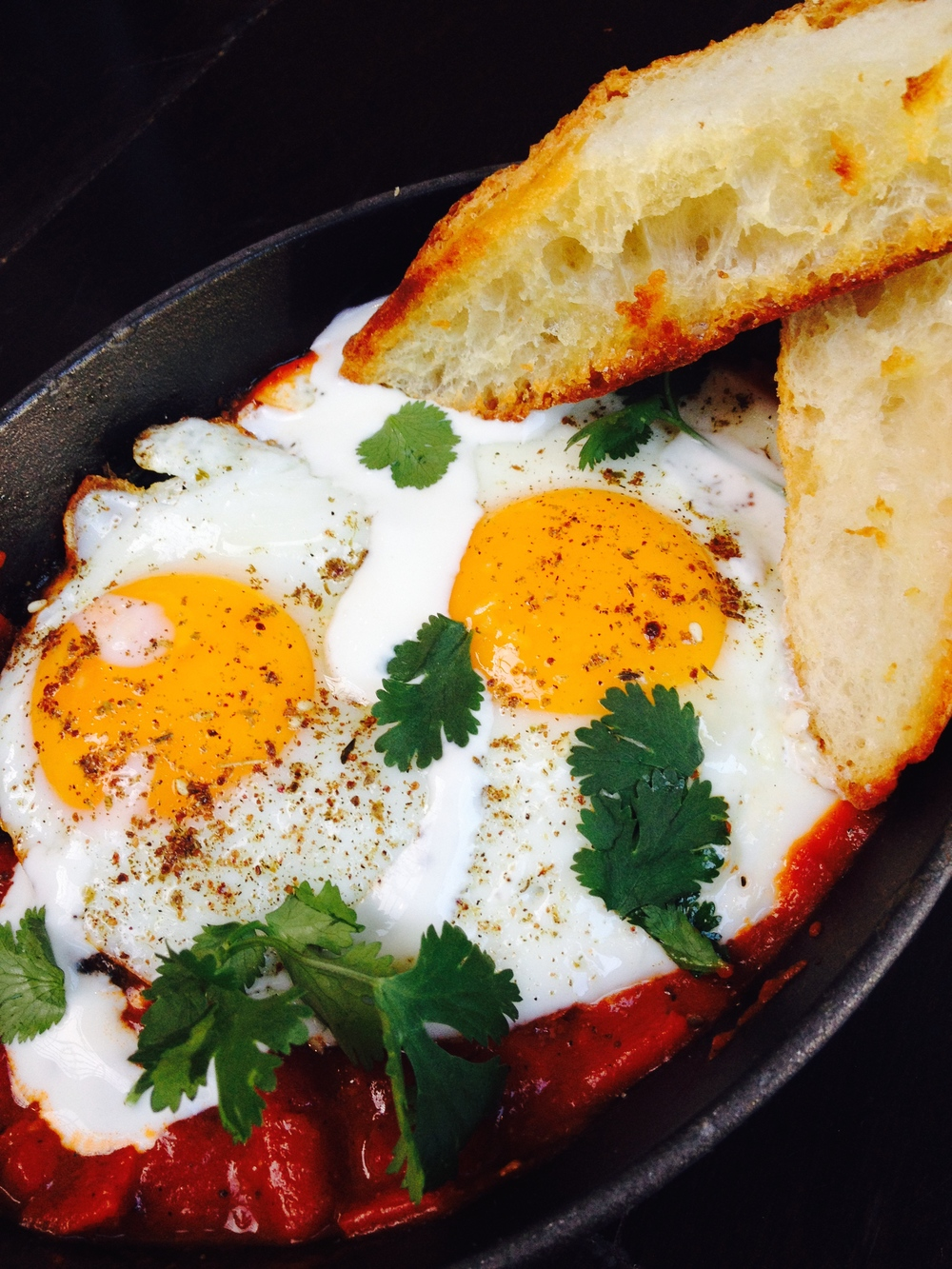 Shakshouka, a Middle Eastern breakfast dish of eggs in a sauce of tomatoes, onions, and cumin, served with grilled bread.