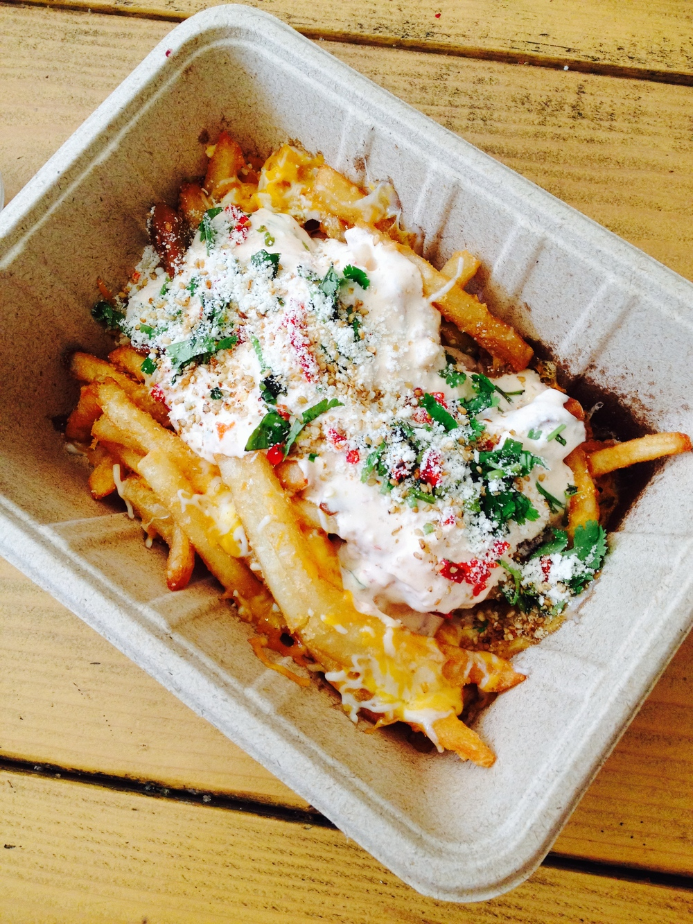 Ooey Gooey Fries - beer-battered with sour cream sambal, monterey jack and cheddar cheese, cotija, chilies, cilantro, and pickled garlic.