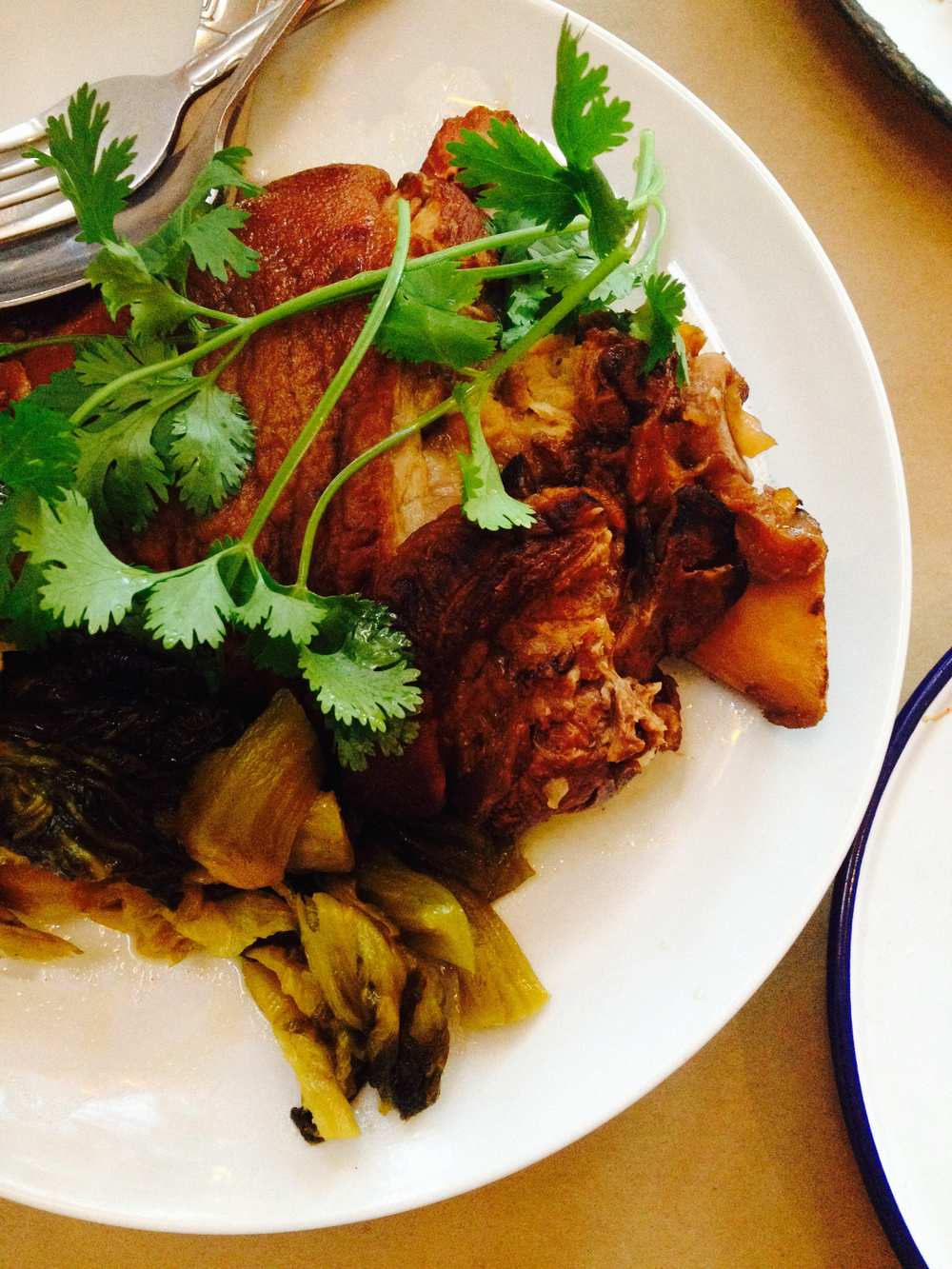 """kar moo parlow, a whole braised pork hock with both skin and fat left on that has been slow-cooked with dark soy, five spice, garlic (as the restaurant states on its menu, """"very rich, very good"""")"""