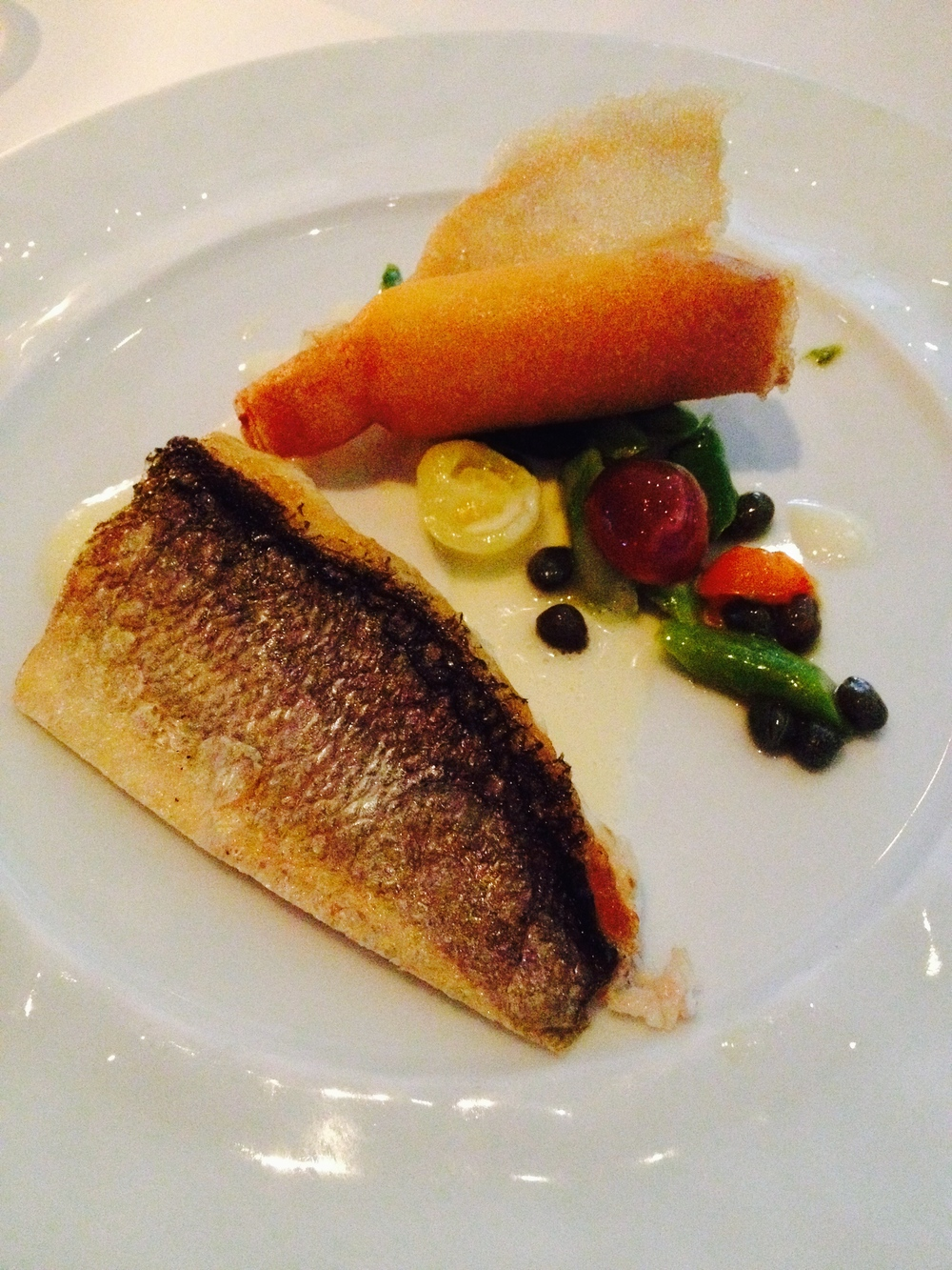 il branzino  with crispy polenta, asparagus, capers, and tomatoes