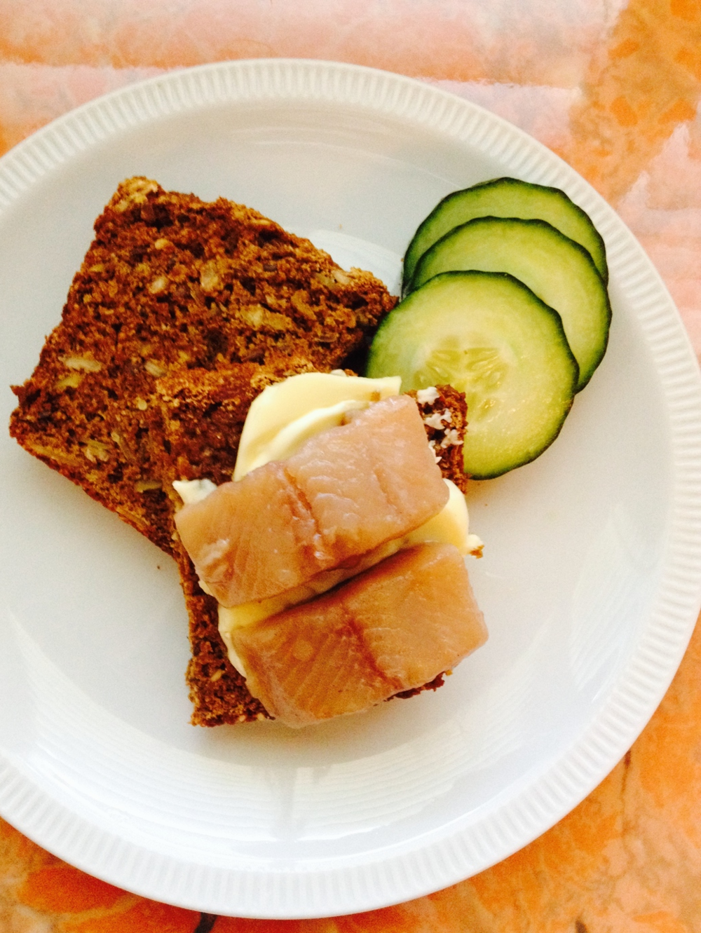 Open-faced sandwich with Danish butter, pickled herring, and cucumber.