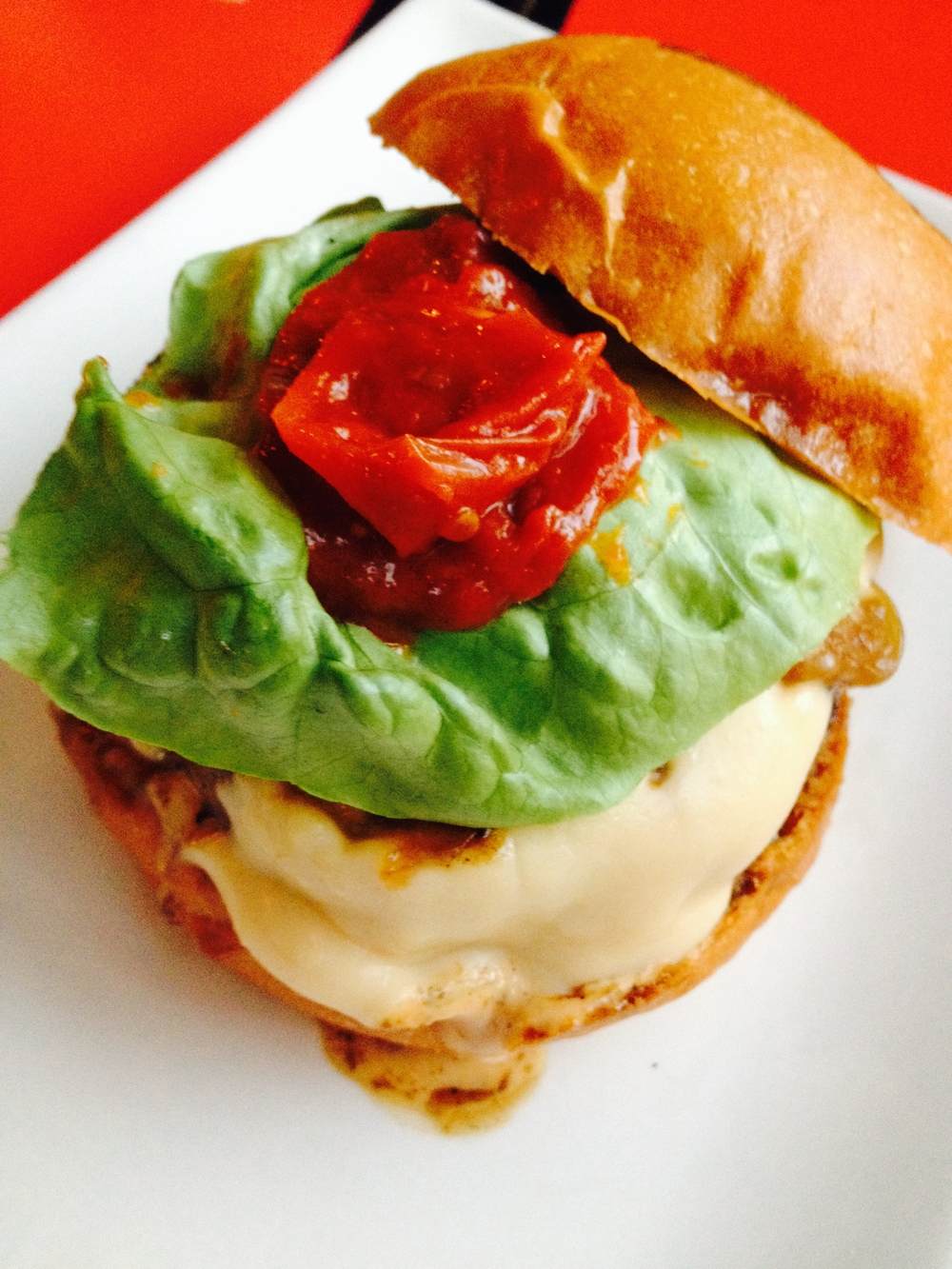 The Cali Burger, with butter lettuce, slow-roasted tomato, house spread, house-made American cheese, caramelized onions.