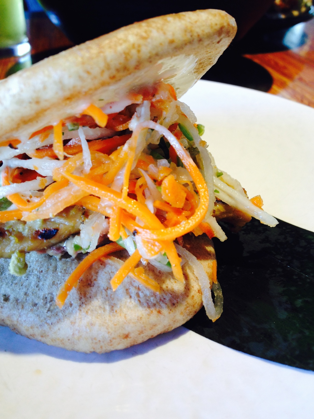 Grilled Pork Banh Mi - grilled pork loin, pate, housemade pickled vegetables, diced chilies, cilantro, and garlic aioli.
