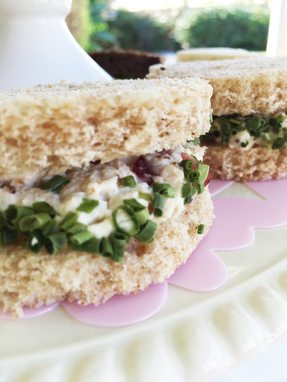 Chicken salad sandwiches with dried cranberries, garnished with chives.