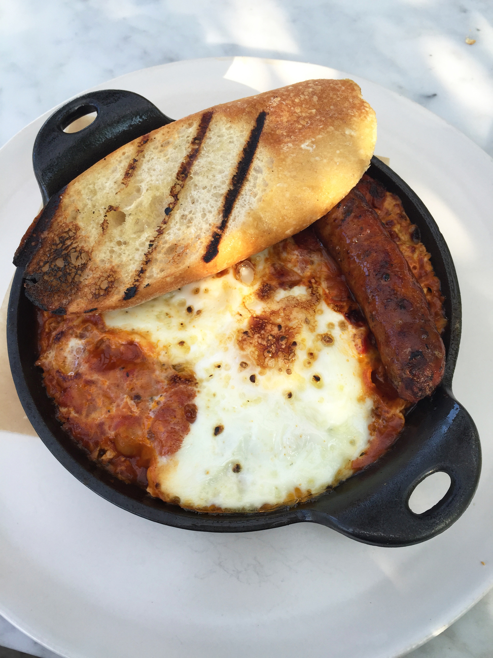 Moroccan Baked Eggs with mergeuz sausage, cage-free farm eggs, tomatoes, chickpeas, peppers, and grilled bread.