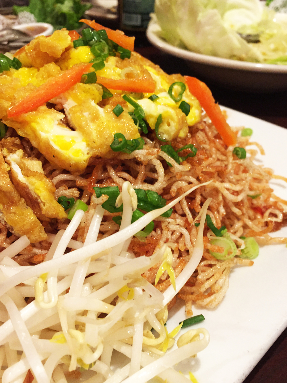 MEE-GROB - Sweet and sour pan-fried crunchy rice noodles, topped with sliced chicken, tofu, egg, and shrimp.