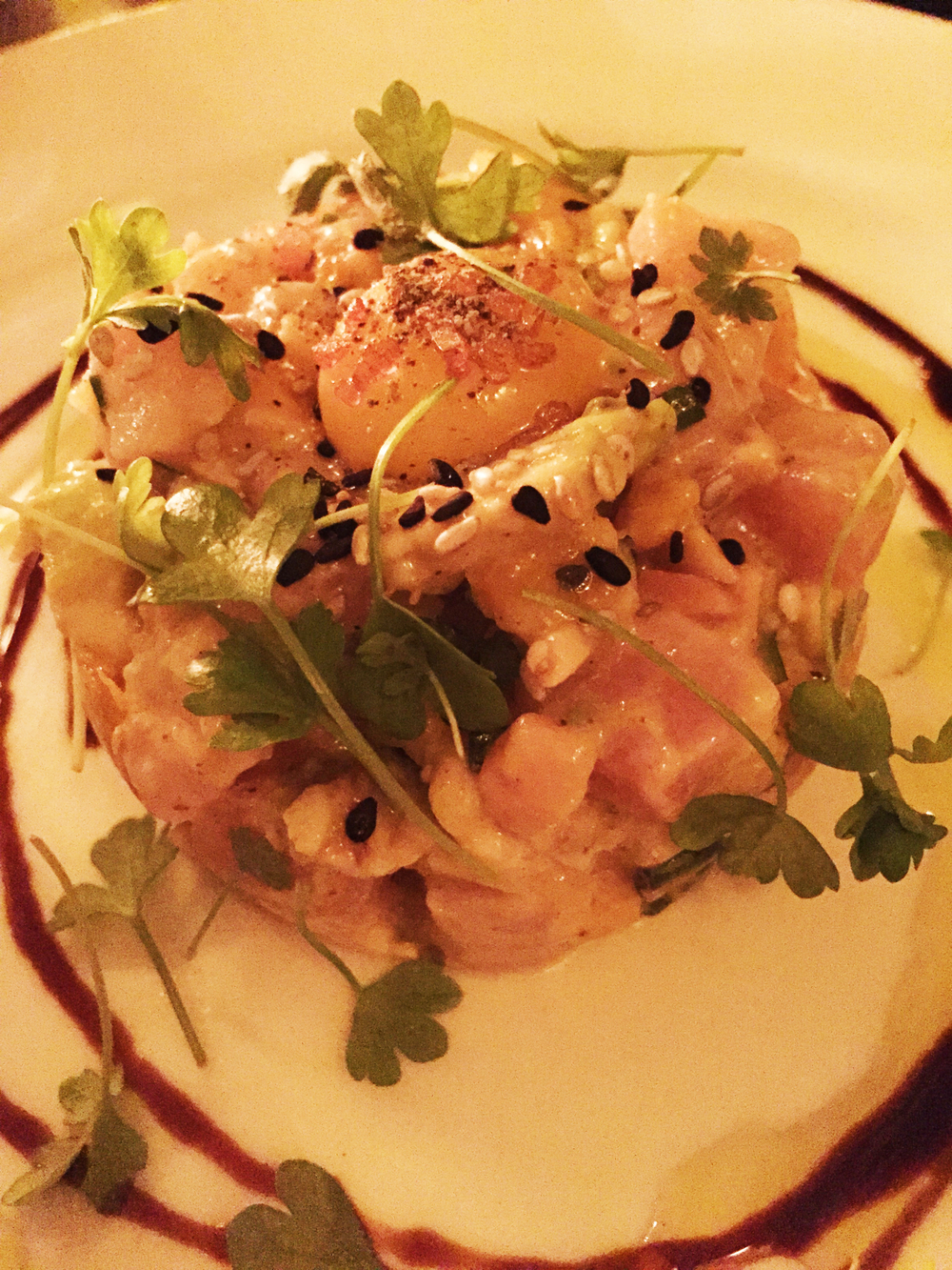 Hamachi Tartare with avocado, pickled cucumber, ancho, quail egg, crispy wontons.