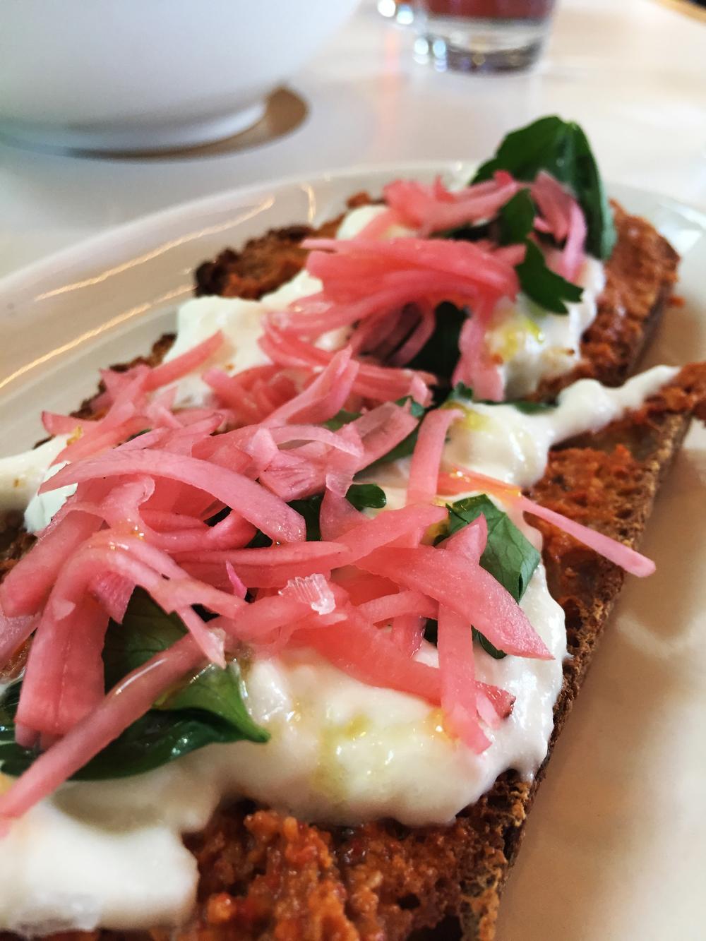 Burrata Toasty with with walnut  muhammara , pickled radish, and parsley.