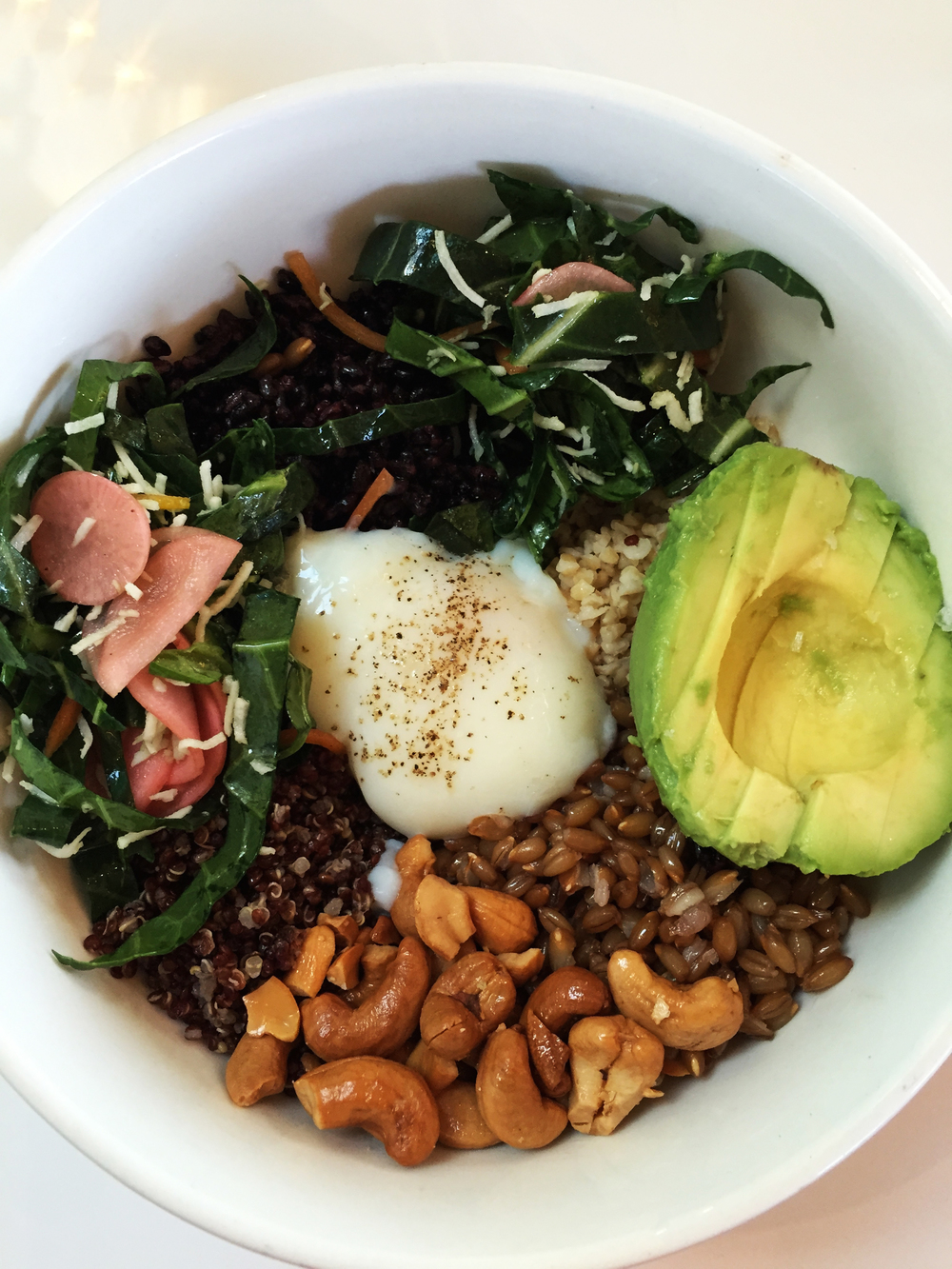 Grain Bowl with runny egg, pickles, collard slaw, cashews, and avocado.